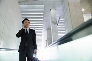 エスカレーターに乗り通話をするスーツ姿の20代男性の写真素材 [FYI01738552]