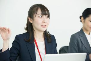 パソコンを使い説明をする笑顔の20代女性の写真素材 [FYI01738567]