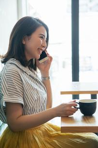 窓際に座り電話をする笑顔の20代女性の写真素材 [FYI01738702]