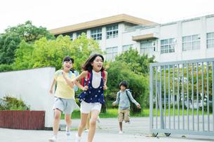 校門から走り出す小学生の写真素材 [FYI01738720]