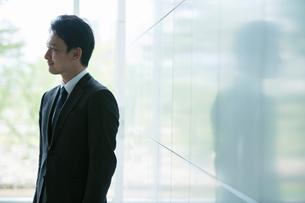窓際に立ち微笑むスーツ姿の20代男性の写真素材 [FYI01738722]