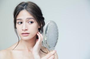 鏡を持ち肌に手を当て状態を確かめる20代女性の写真素材 [FYI01738740]