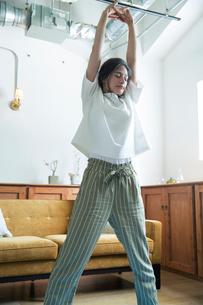 部屋でストレッチをする20代女性の写真素材 [FYI01738745]