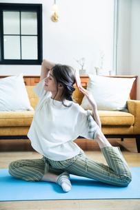部屋でヨガのポーズをする20代女性の写真素材 [FYI01738752]