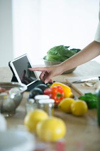 台に並べられた野菜と果物とタブレットを押す女性の指先の写真素材 [FYI01738758]