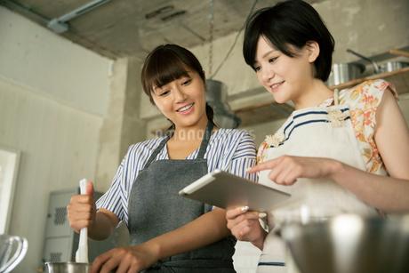 タブレットを確認しながらお菓子作りをする20代女性2人の写真素材 [FYI01738761]