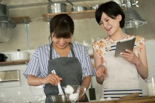 タブレットを確認しながらお菓子作りをする20代女性2人の写真素材 [FYI01738763]
