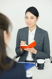 仕事中にメモを取る笑顔の30代女性の写真素材 [FYI01738770]