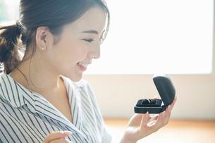 指輪をみつめ笑顔の20代女性の横顔の写真素材 [FYI01738793]