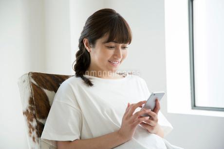 部屋でスマホを持ちくつろぐ20代女性の写真素材 [FYI01738840]