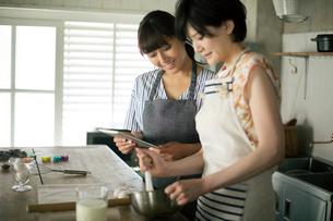 タブレットを確認しながらお菓子作りをする20代女性2人の写真素材 [FYI01738868]