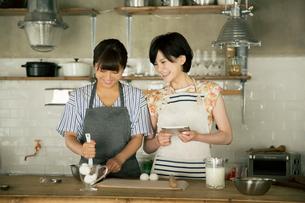 タブレットを確認しながらお菓子作りをする20代女性2人の写真素材 [FYI01738875]