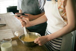 タブレットを確認しながらお菓子作りをする女性2人の手元の写真素材 [FYI01738890]