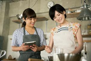 タブレットを確認しながらお菓子作りをする20代女性2人の写真素材 [FYI01738914]