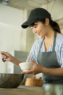 お菓子を作る笑顔の20代女性の写真素材 [FYI01738917]