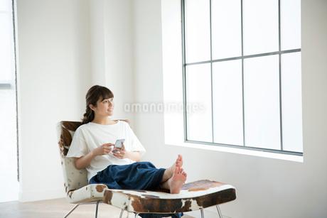 部屋でスマホを持ちくつろぐ20代女性の写真素材 [FYI01738948]