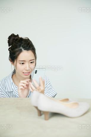 靴の写メを撮る真剣な表情の20代女性の写真素材 [FYI01738970]
