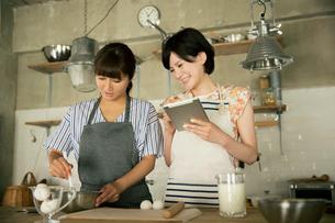 タブレットを確認しながらお菓子作りをする20代女性2人の写真素材 [FYI01738978]