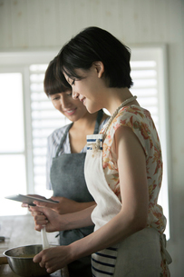タブレットを確認しながらお菓子作りをする20代女性2人の写真素材 [FYI01738979]