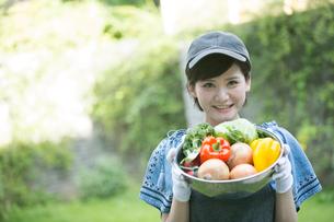 採れたての野菜を持つ笑顔の20代女性の写真素材 [FYI01738992]