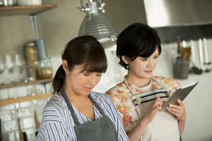 タブレットを確認しながらお菓子作りをする20代女性2人の写真素材 [FYI01739012]