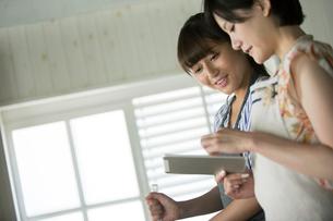 タブレットを確認しながらお菓子作りをする20代女性2人の写真素材 [FYI01739026]
