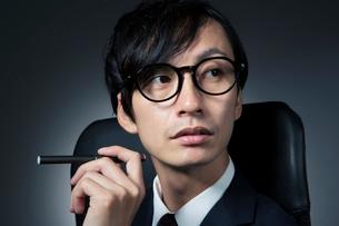 電子たばこを持つスーツ姿の男性の写真素材 [FYI01739033]