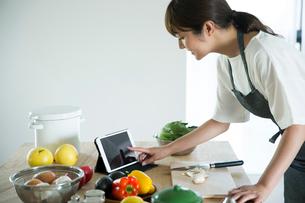 台に並べられた野菜と果物とタブレットを押す女性の指先の写真素材 [FYI01739041]