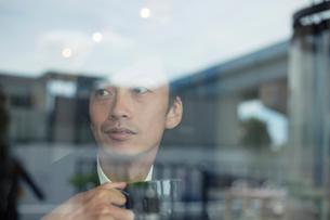 カフェでくつろぐスーツ姿の男性の写真素材 [FYI01739043]