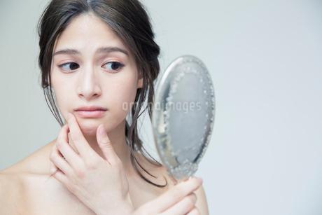 鏡を持ち肌に手を当て状態を確かめる20代女性の写真素材 [FYI01739070]