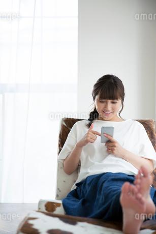 部屋でスマホを持ちくつろぐ20代女性の写真素材 [FYI01739082]
