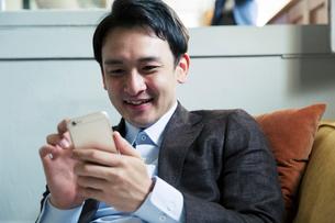 ソファに座りスマホを操作する笑顔の20代男性の写真素材 [FYI01739083]