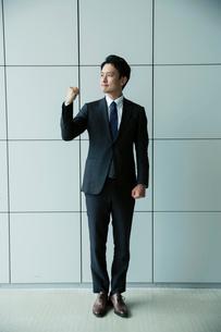 ガッツポーズをするスーツ姿の20代男性のポートレートの写真素材 [FYI01739086]
