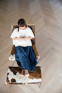 大きな部屋でスマホを持ちくつろぐ20代女性の写真素材 [FYI01739100]
