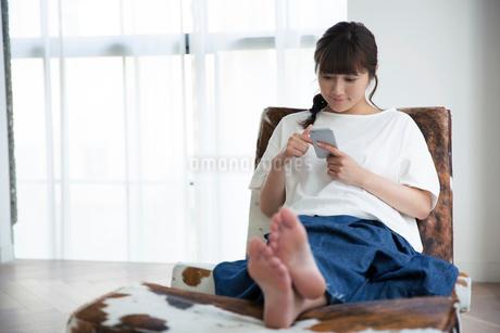 部屋でスマホを持ちくつろぐ20代女性の写真素材 [FYI01739122]