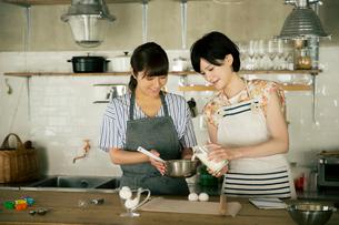 お菓子を作る笑顔の20代女性2人の写真素材 [FYI01739123]