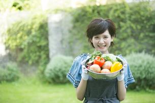 採れたての野菜を持つ笑顔の20代女性の写真素材 [FYI01739131]