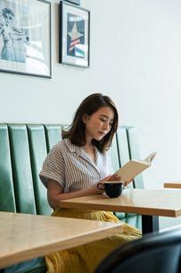 窓際に座り読書をする20代女性の写真素材 [FYI01739218]