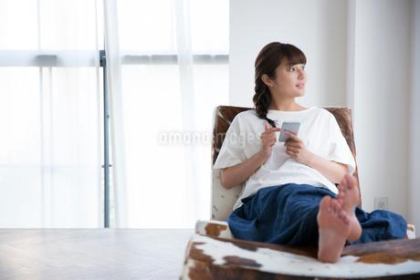 部屋でスマホを持ちくつろぐ20代女性の写真素材 [FYI01739436]