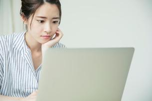 頬杖をつきパソコンを眺める20代女性の写真素材 [FYI01739587]