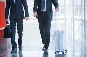 屋内を歩くスーツ姿の男性2人の写真素材 [FYI01739622]