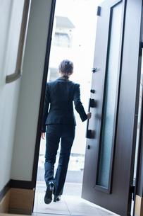 玄関のドアを開ける20代女性の後ろ姿の写真素材 [FYI01739798]