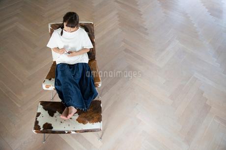 大きな部屋でスマホを持ちくつろぐ20代女性の写真素材 [FYI01739820]