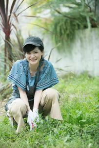 外で庭作業をする笑顔の20代女性の写真素材 [FYI01739920]