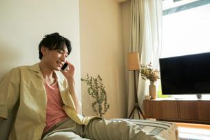 部屋で電話をする笑顔の20代男性の写真素材 [FYI01739922]