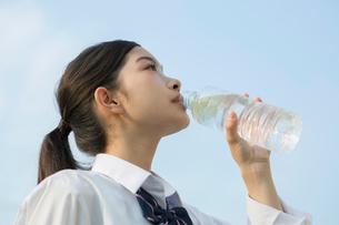 青空の下ペットボトルの水を飲む女子高校生の写真素材 [FYI01739924]