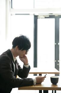 カフェでスマホを見る20代男性の写真素材 [FYI01739945]