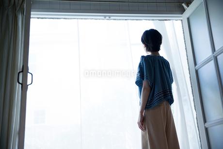 窓際に立つ20代女性の後ろ姿の写真素材 [FYI01739959]