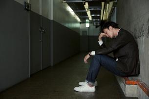 暗い廊下にしゃがみ考え込む男性の写真素材 [FYI01740014]