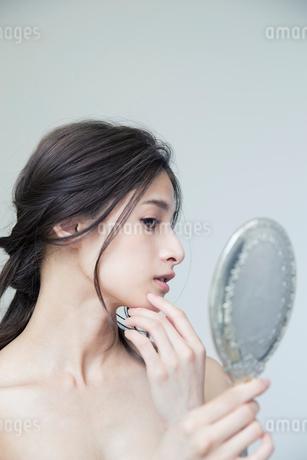 鏡を持ち肌に手を当て状態を確かめる20代女性の写真素材 [FYI01740029]